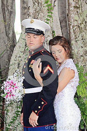 Bride with arms around military groom