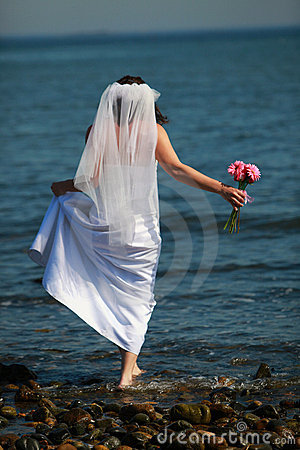 Bride barefoot in water