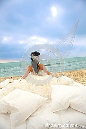 Bride in bed at the coastline.