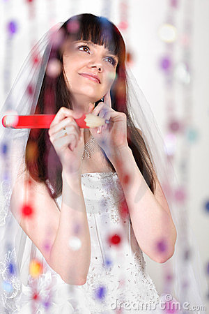 Bride with big pencil stands behind curtain