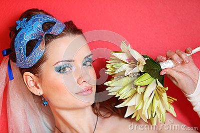 Bride with blue makeup and mask in hairdo holds bo