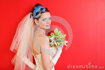 Bride with blue  mask in hairdo holds bouquet