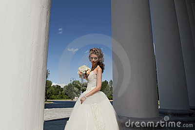 The bride with a bouquet at columns.