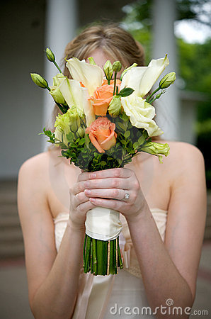 Bride with bouquet in front of her face