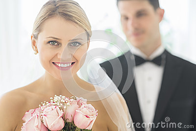 Bride With Bouquet Of Roses While Groom Standing In Background