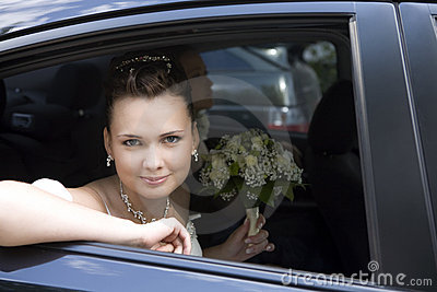 Bride with bouquet sitting in wedding car