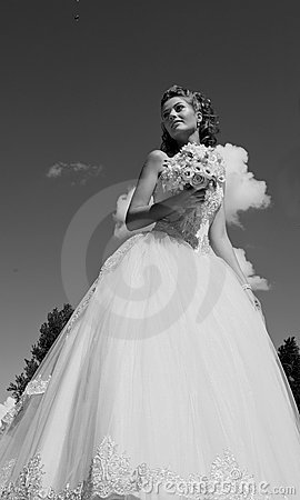 The bride with a bouquet and the sky.