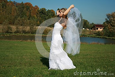 Bride with bridal veil flying walking on a meadow