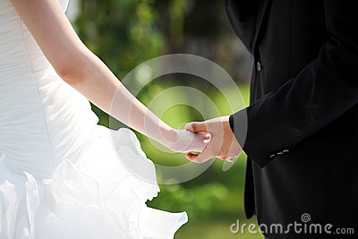 Bride and bridegroom hand in hand