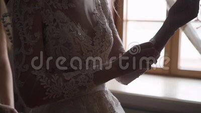 Bride buttoning sleeves on her wedding dress. Put on wedding dress, wearing gown.  stock video footage