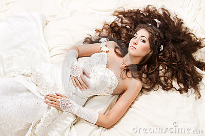 Bride with curly long hair lying over white.