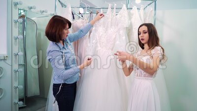 Bride and dressmaker choosing wedding gown in salon. Selective focus on female dressmaker showing beautiful wedding dresses to young bride in white gown in salon stock footage