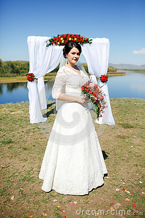 Free Bride During Ceremony Outdoors With Bouquet On River, Arch Of Roses And White Cloth. Royalty Free Stock Photos - 66524098