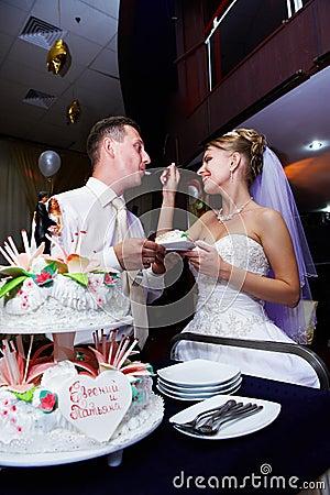 Bride feeding her fiance wedding cake