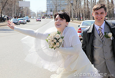 Bride with fiance on street stops car