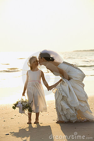 Bride and flower girl on beach.