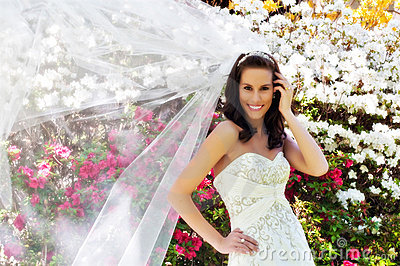 Bride in front of flowers with veil