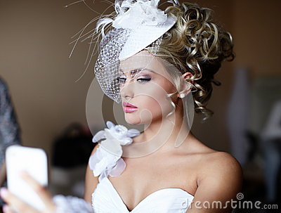 Bride girl in wedding dress looking in mirror