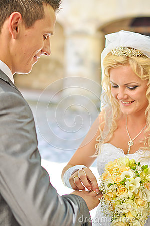 Bride giving ring to groom