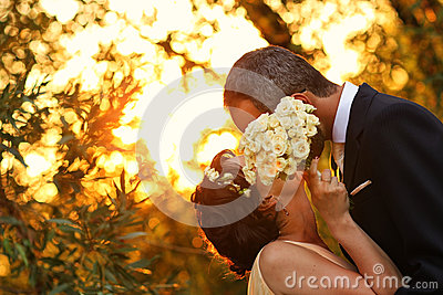 Bride and groom in a beautiful light holding hug