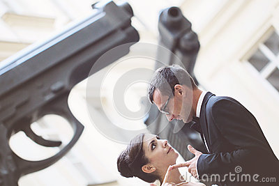 Bride and groom in the city near two giant gun pistols