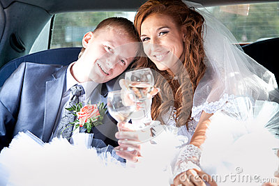 Bride and groom clinking glasses in limousine