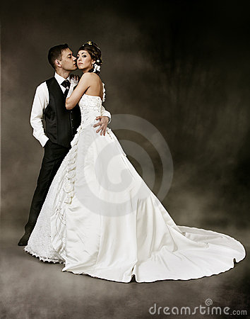 Bride and groom at dark background. Wedding couple