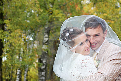 Bride and groom embrace in autumn forest