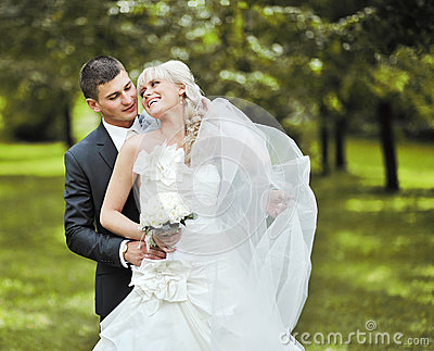 Bride and groom embrace each other and laughing on their wedding