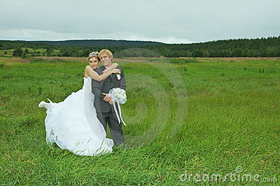 Bride and groom embrace on field