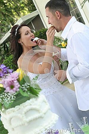 Bride and groom feeding cake