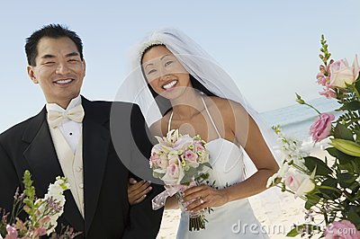 Bride and Groom with flowers on beach (portrait)