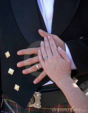Bride and groom hands resting on groom stomach