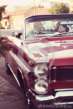 The bride and groom have fun behind the wheel of red retro vintage car. Wedding.