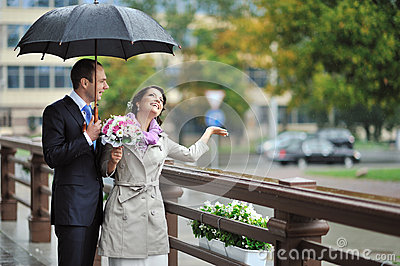 Bride and groom hiding from the rain, while catching raindrops a