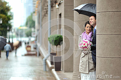 Bride and groom hiding from rain in an old town