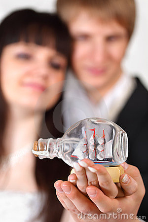 Bride and groom hold little vessel in bottle