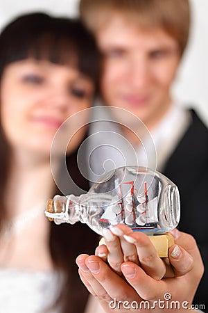 Bride and groom hold little vessel in bottle