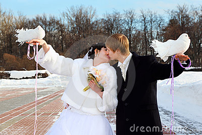 Bride and groom hold white doves and kiss