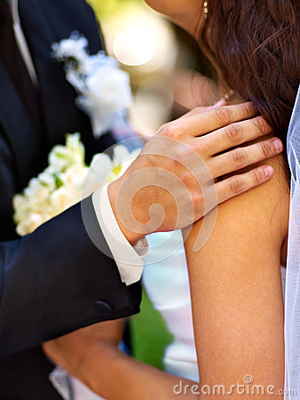 Bride and groom holding flower outdoor.