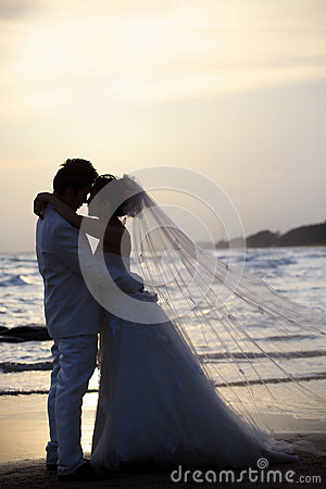Bride and groom holding and hug at sea side in dus
