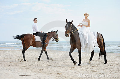 Bride and groom on a horses by the sea