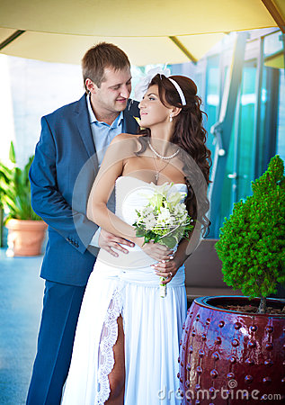 Bride and groom are hugging near the glass wall