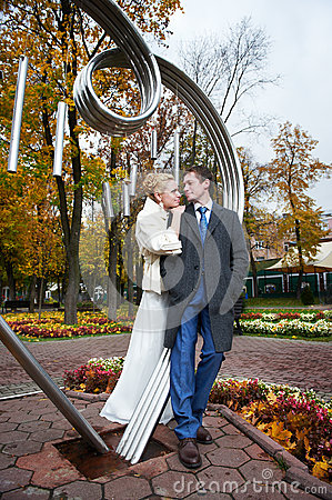 Bride and groom about iron figure on autumn