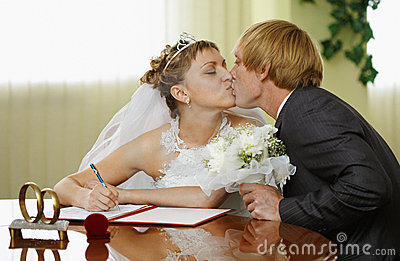 Bride and groom kiss during ceremony of marriage