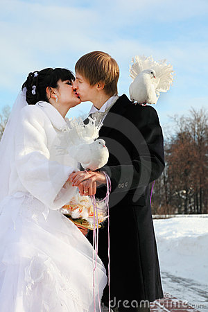 Bride and groom kiss and hold white dove at winter