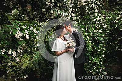 bride and groom kissing against big bush with flowers