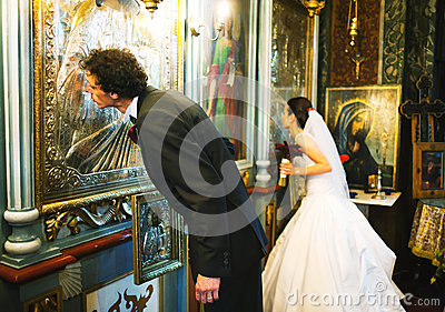 Bride and groom kissing altar wall