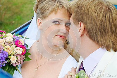 Bride and groom kissing in the car