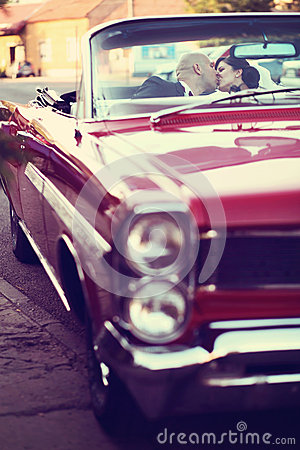 The bride and groom kissing and have fun behind the wheel of red retro vintage car. Wedding.